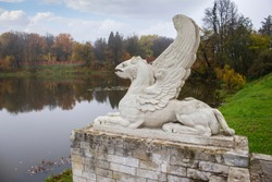 Stone concrete lion with wings statue, gargoyle on the stone pedestal, decoration of the manor park, the shore of the pond of the lake autumn landscape. Sculptural composition on the lake