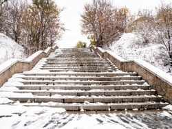 Stone concrete snow-covered stairs with footprints in the city in late autumn or winter. Stairway to heaven.