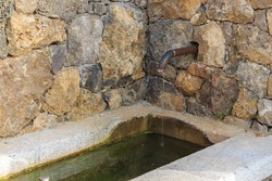 Stone-Covered Village Fountain with Antique Tap