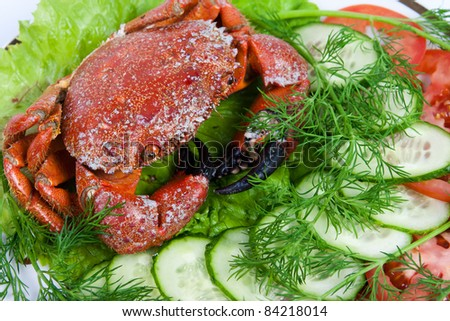 Stone crabs on a plate decorated with vegetable slicing