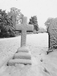 Stone cross in a cemetery covered in snow - black and white