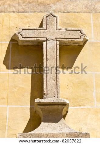 Stone cross on a wall - stock photo