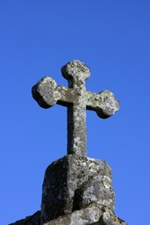 Stone cross on deep blue sky