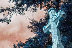 Stone cross. Religious faith spiritual image of a cemetery memorial against sunset sky. Christian graveyard scene of beautiful blue tone tree foliage behind a grave headstone with a heavenly sepia sky