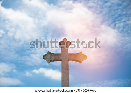Stone cross with sun background against blue sky and clouds. Conceptual stone cross religion symbol.