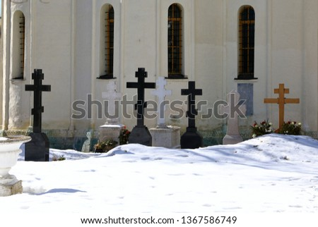 Stone crosses on tombstone, stone cross in a  snow graveyard.