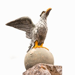 Stone eagle sculpture in powerful pose guarding entrance gate of residence.