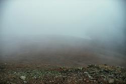 Stone field in dense fog in highlands. Empty stone desert in thick fog. Zero visibility in mountains. Minimalist nature background. Dark atmospheric foggy mountain landscape. Lichens on sharp stones.