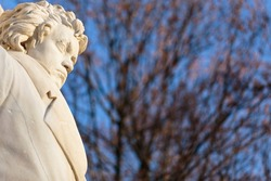 Stone figure of musical genius, composer and pianist Ludwig van Beethoven, in a monument from 1898. Horizontal daylight view with blurry leafless trees in the background and blue sky