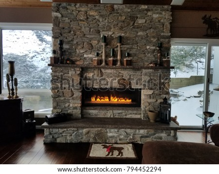 Stone Fireplace with Flames a-Glow, Rustic Style in Brown and Grey Tones, Cozy Home in Winter