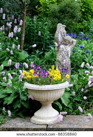 Stone Flower container with pansies and a stone statue