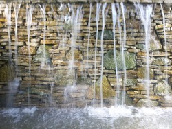 Stone fountain. Beautiful fountain over the colorful wall.