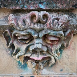 Stone front of a public fountain in a park in Cuenca, (Spain), where the water pipe is located at the mouth of a monstrous face