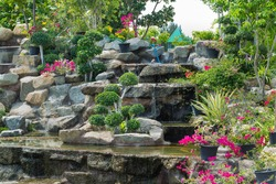 Stone garden with waterfalls and flowers pot decoration in cozy home flower garden on summer.