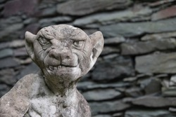 Stone gargoyle and dry stone wall
