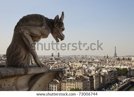 Stone gargoyle with horns peering over the city of Paris towards the Eiffel Tower while perched on a corner of the cathedral of Notre Dame.