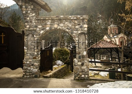 Stone gateway, entrance to the church yard. Mountain, forest, stone, Sunrise in cold winter day.