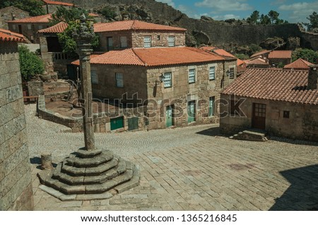 Stone gothic houses and chapel encircling a deserted square on slope with pillory, in a sunny day at Sortelha. One of the most astonishing and well preserved medieval villages in all Portugal. Stockfoto ©