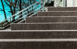 Stone granite stairs steps background with metallic aluminium handle. Red brown modern stairs. Entrance to the shop in the city street on blue sky and trees background