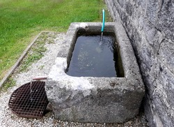stone granite water tank by the cemetery wall. The inflow from the spring with a rubber hose feeds the old stone fountain made of carved block
