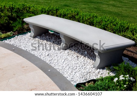 stone gray bench strewn with white stone pebbles in a garden with boxwood bushes and a green lawn with plants, close up of a place for sitting and resting near a marble tile walkway on a sunny summer. #1436604107