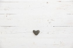 Stone heart decoration on an aged wooden table. Background for postcards with space for text. Festive season. Heart of natural stone in the center of the frame