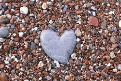 Stone heart on pebble background