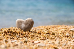 Stone heart on the pebble beach in the background the sea close up/ A stone in the shape of a heart close up/ Stone heart