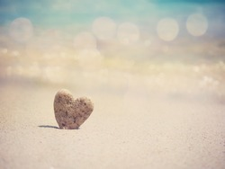 Stone heart shape standing on summer beach sand, love concept.