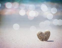 Stone heart shape standing on summer beach sand, love concept, vintage filter effect.