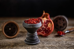 Stone hookah head on old rustic table with fruit flavoured tobacco