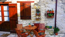 Stone house in Greek style with a  wooden door, table and chairs