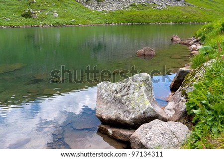 stone in lake in green mountains