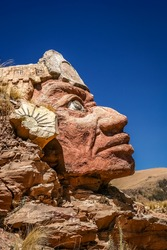 Stone Inca face sculpture on the shore of Lake Titicaca in Peru
