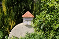 Stone letterbox in the shape of a house surrounded by green plants