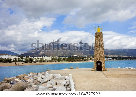 Stone lighthouse and pier in Puerto Banus near Marbella in Spain.