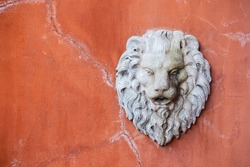 Stone lion head sculpture figure on wall, The lion head sculpture on the orange cracked cement wall