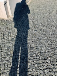 Stone made streets with black human shadows on it