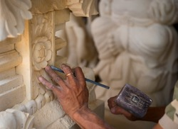 Stone mason at work carving an ornamental relief