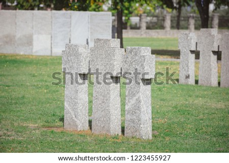 stone memorial monuments placed in row on grass at cemetery #1223455927