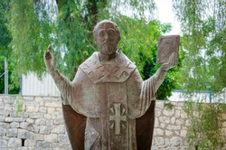 Stone monument and image of Saint on the street at the entrance to of Ancient Byzantine Church of St. Nicholas Wonderworker, Santa Claus. Old Greek antique temple in city of Demre, Antalya, Turkey.