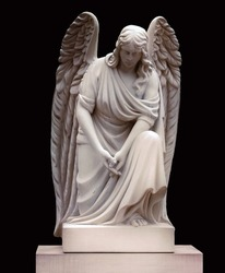 Stone monument of an angel at the cemetery. Isolated on black background