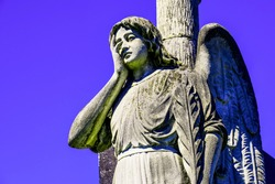 Stone monument of an angel with a cross in the cemetery