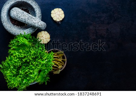 Stone mortar bowl and pestle with garlic, bay and salad leaves Stockfoto ©