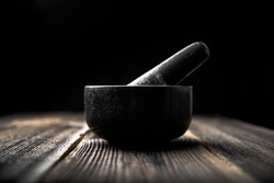 Stone mortar with pestle on black background