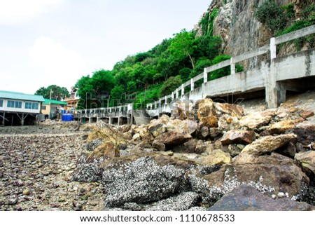 Stock Photo Stone mountain with bright cloud sky, Road with concrete barrier beside sea and rock mountain, Green tree cover on stone mountain, Road on seaside with rock and stone