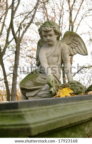 Stone mourning angel statue sitting on tombstone - stock photo