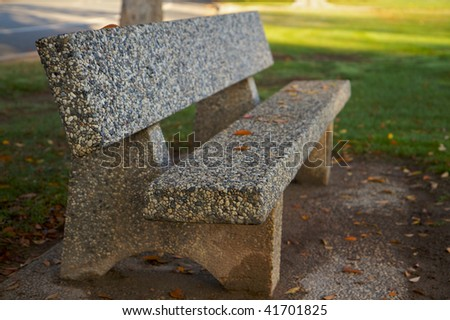 Stone Park Bench  with fallen leaves and green grass does as a high dynamic range image - stock photo