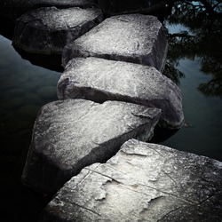 Stone path across a tranquil pond
