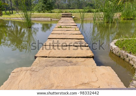stone path across river to green garden